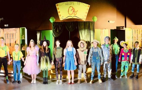 The cast of the first seventh grade play, Oz, standing together on stage in their costumes.