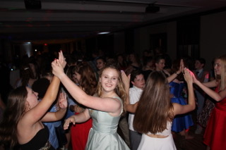 Some 8th graders smile for a picture during a slow dance