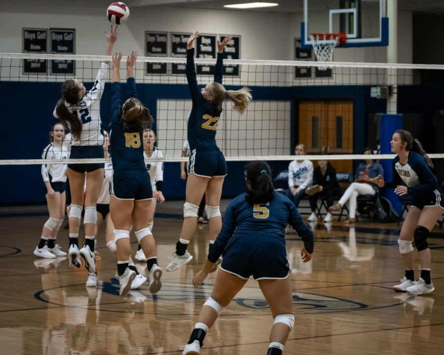 Our Lady Mustangs go up to stuff Prince of Peaces spike.