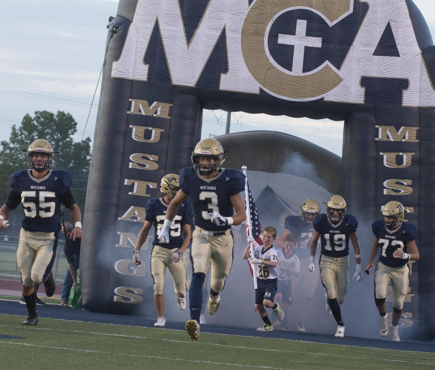 The Mustangs running out of the tunnel as they take on Temple Christian