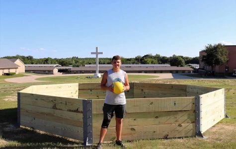 Senior, Will Boese poses in front of his gaga pit after a long day of building it.