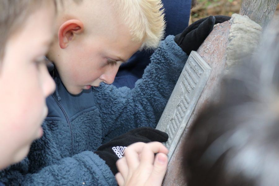 Trase Ackmann focusing on reading a stone tablet during the trail tour.