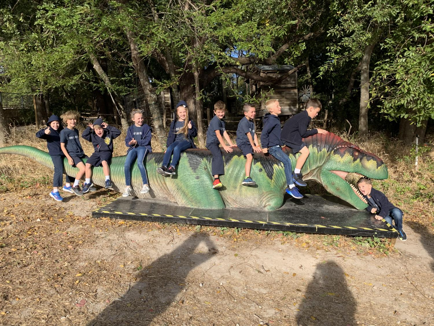Second graders taking a picture while sitting on an electronic dinosaur.