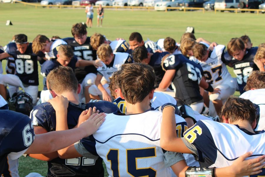 The Mustangs praying with Providence after a big win at home.