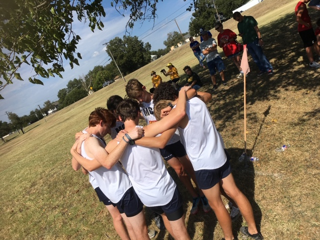 The varsity boys huddle together to get a prayer in before the race. They start every race with this, so they know they're not just running this race for themselves, but also for Christ.