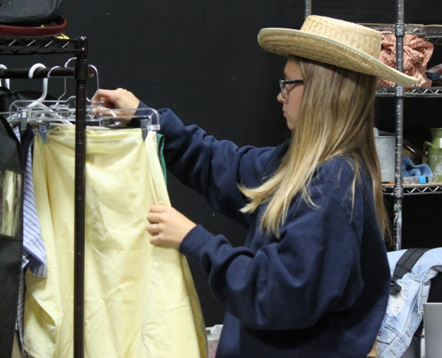 Sophomore, Charli Bazor, prepares the costumes for the actors.
