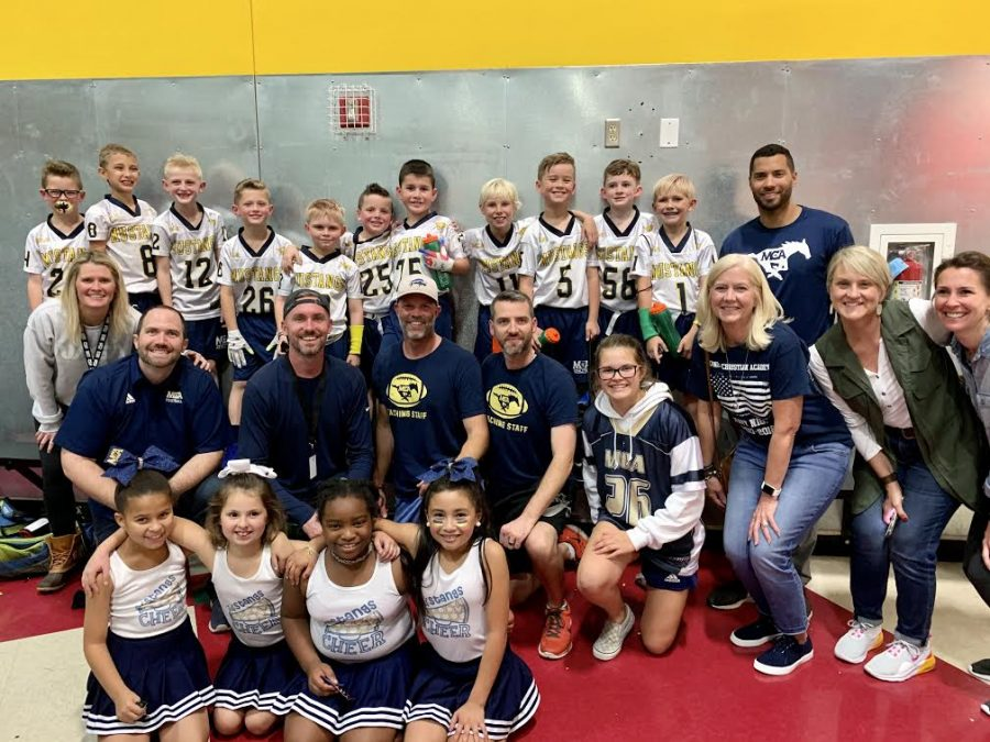 The Lil Stangs' football players and cheerleaders take a picture with coaches and family after winning the championship game.