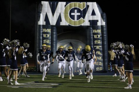 The Mustang football team runs out of the tunnel for the last home game of the season.