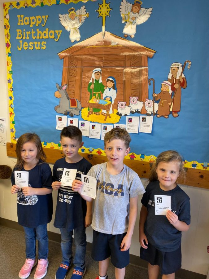 A few of Mrs. Hamilton's kindergarten students take a picture while holding their