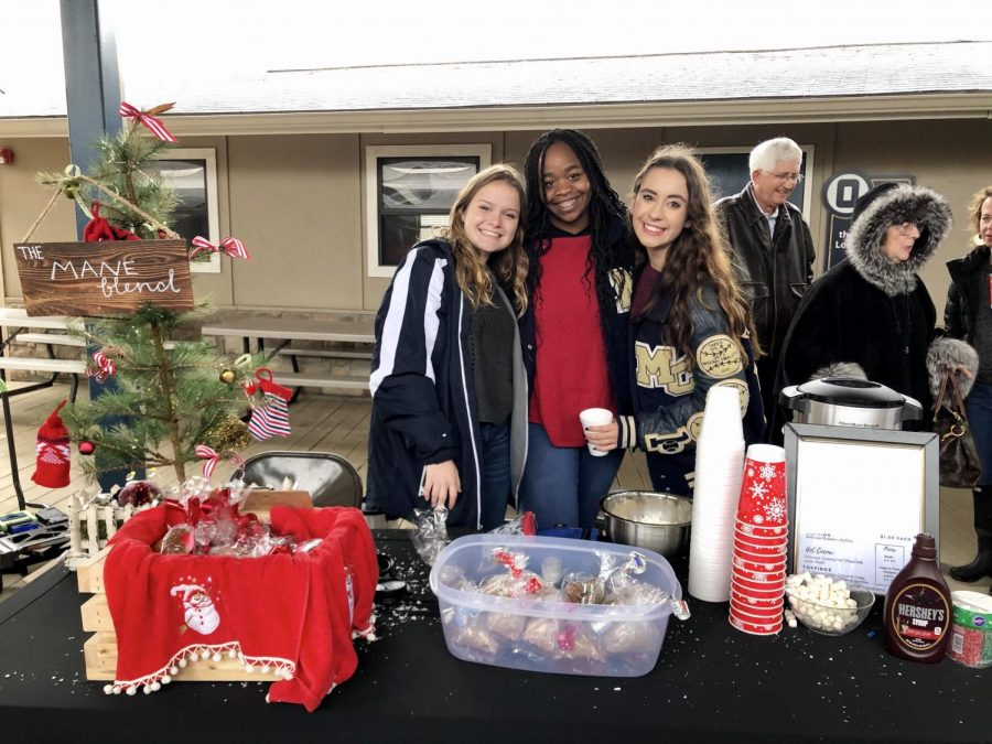 Seniors, Emma Bryant, Jasmine Holmes, and Sydney Wible, pose for a picture behind their booth, The Mane Blend.