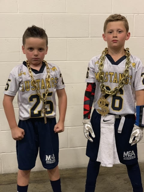 Mason McAnally and Ben Nordhaus look game ready as they are wearing their uniforms and extra gear.