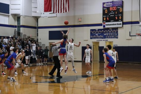 Senior Dustin Rogers goes up to get control of the ball at tip off.