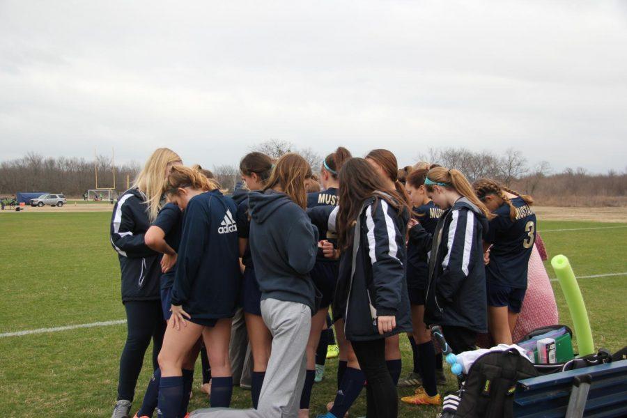 Lady Mustangs varsity girls huddle around to pray before the game.