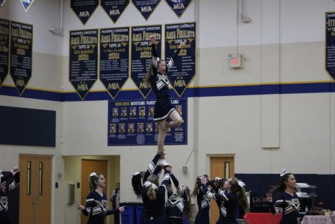 Varsity Cheer stunting with sophomore, Campbell May   at the Wild Week Pep Rally.