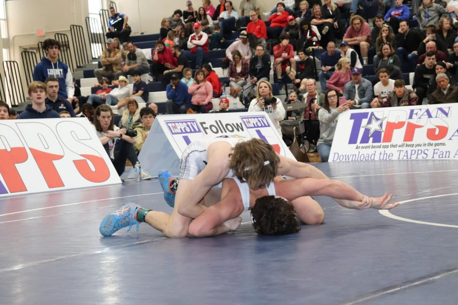 Junior Nate Gwynn pinning his opponent in his final match to claim the state champion title.
