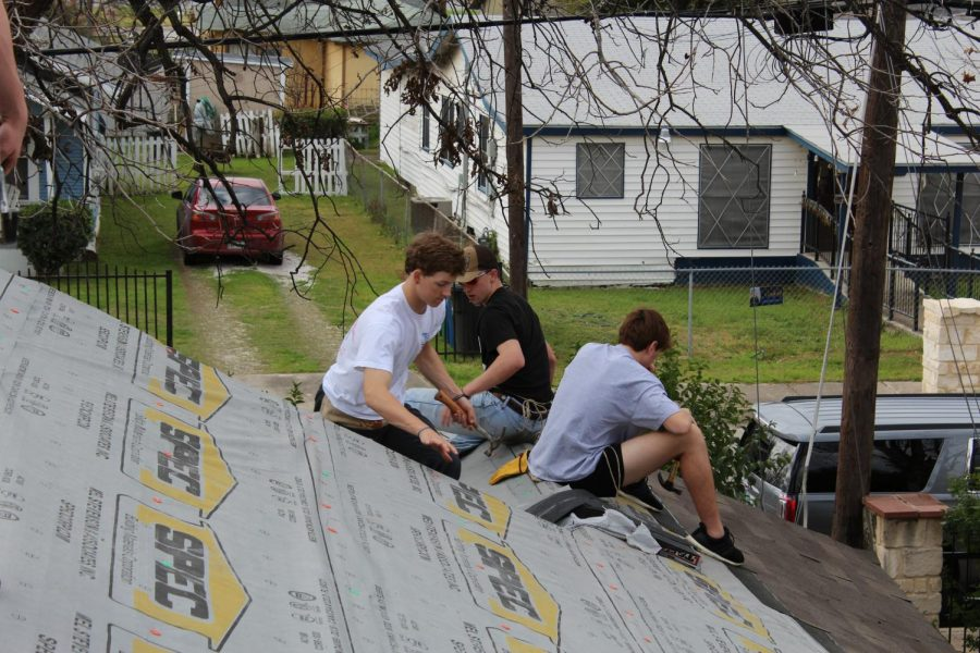 Juniors Blake McGraw, Connor Durbin, and Cooper Roach work together to install shingles on a small area of the roof.