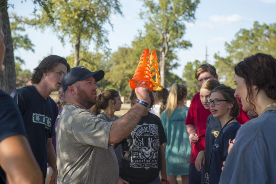 Upper English teacher Tyler Blue stands with the senior students while explaining the capture the flag game at Upper School Retreat.