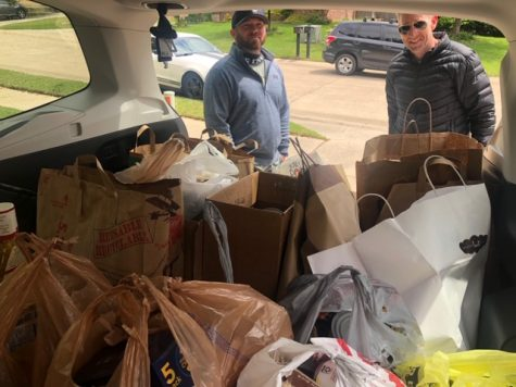Coach Blue and and Coach McKeller take a picture beside a car full of donated goods.