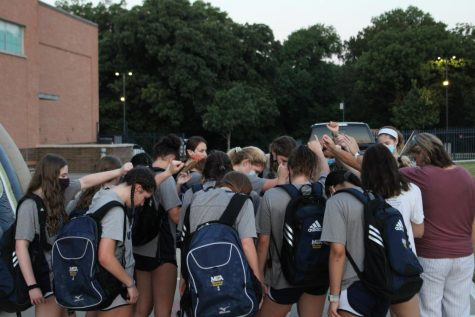 The Volleyball team praying after receiving uniforms and enjoying breakfast with one another.