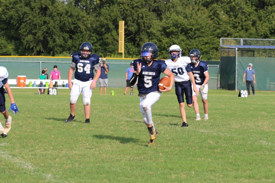 Eighth grader Jeremiah Daoud runs the ball to get the first down.