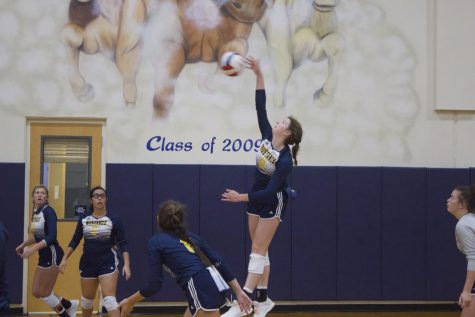 Senior Ava Grace Haggard jumping up to hit the ball.