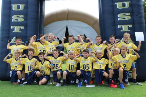 The Fourth Grade Blue and Gold Teams show off their muscles and their new uniforms.