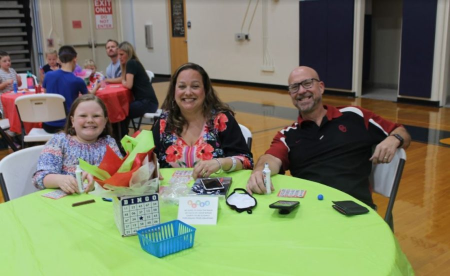 Fourth grader Madelyn Anderson takes a picture with her parents at Bingo Night.