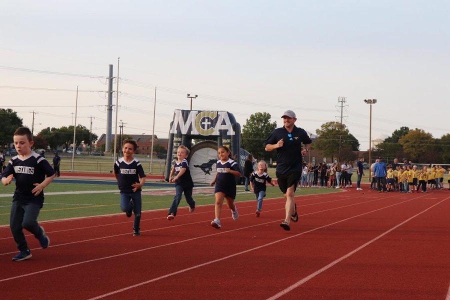 First grade soccer team and coach Jared Maier run after their team gets announced.