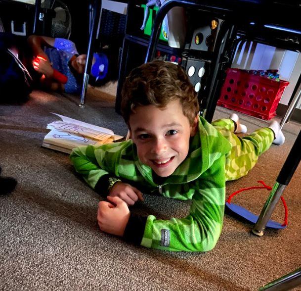 First Grader Benjamin Barli poses for a photo while laying under his desk.