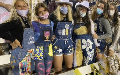 A group of senior girls posing for a picture in their senior overalls while cheering on their mustangs.