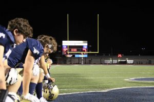 The team kneels to pray by the scoreboard after the game.