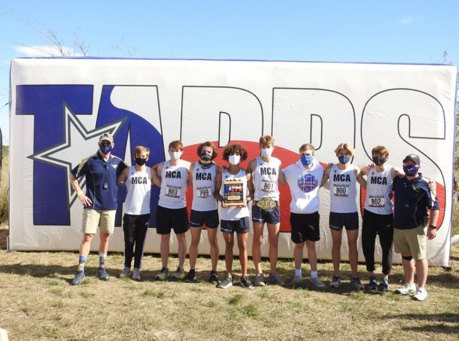 The boys cross country team poses after winning state runner up at the state championship race.