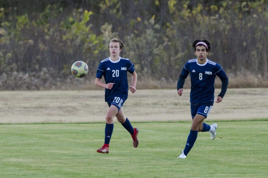 Freshman Liam Corley and sophomore Emilio Sanchez charge the ball.