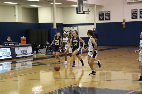 Eighth grader, Casey Gerardis dribbles the ball up the court.