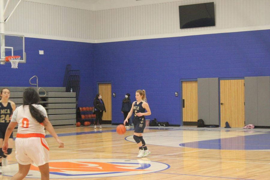 Maddie Clark dribble the ball up the floor.