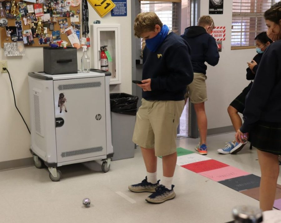 Eighth grader Cash Harrison uses his phone to code the rolling robot.
