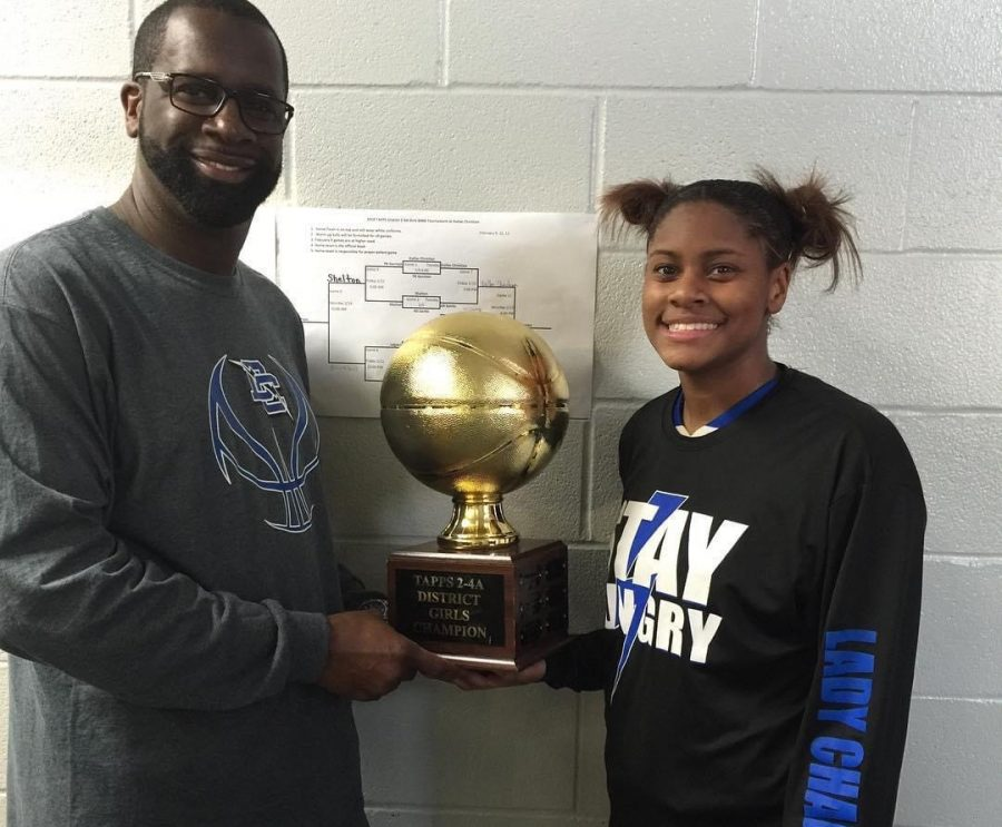 MCA head girls basketball coach Ashlan Miles holding the district championship trophy with her father, Calvin Miles, in 2016