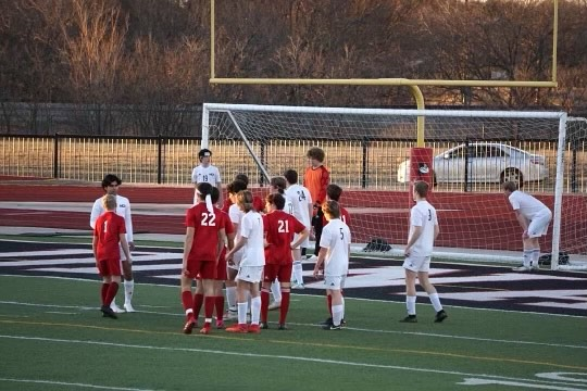 The varsity boys set up to defend a corner kick.