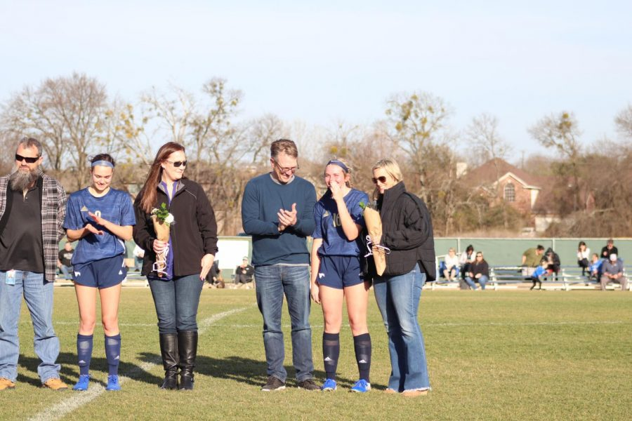 Senior Hallie Witte stands with her parents, Anne and Eric, for senior night.