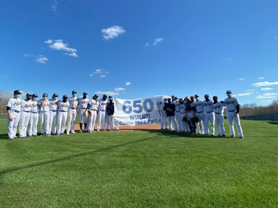 The baseball team poses for a picture holding Coach Pirtle's new milestone.