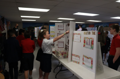 Fifth graders Megan Moates and Isabella Melton look at their friends project.