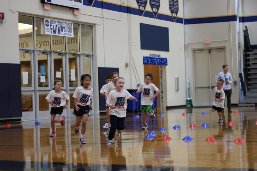 First grade girls smile while running.