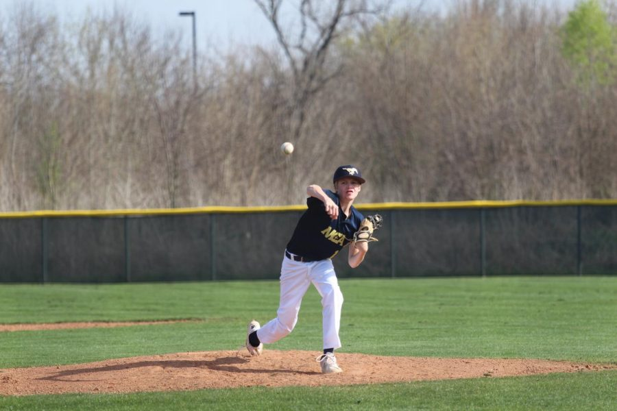 Eighth grader, Jackson John pitches the ball during the game.