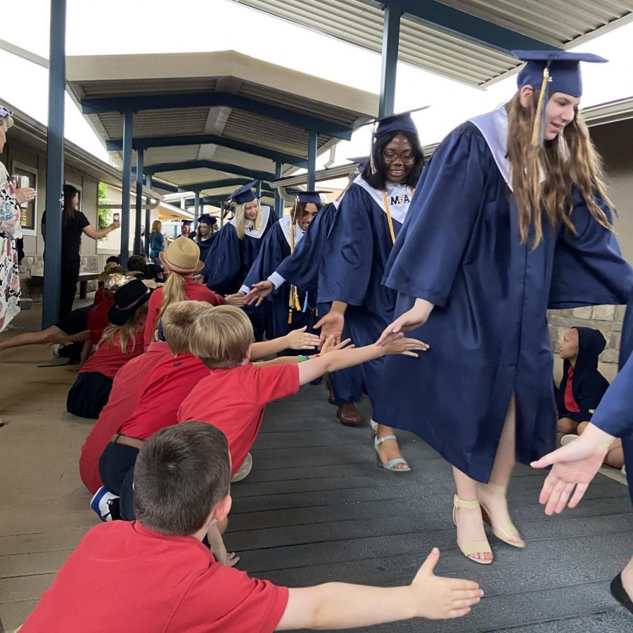 The lower school students reach out their hands for a high five as the seniors pass by.