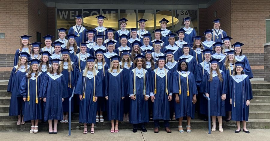 The graduating class of 2021 take the senior class picture in their cap and gown.