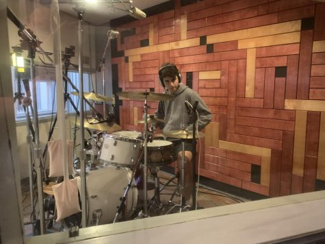 Senior Ethan Selz playing the drums during a song they recorded in their album.