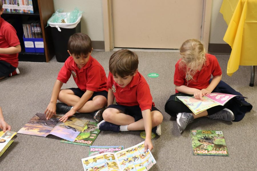 Kinder students look at their books they purchased at the Book Fair.