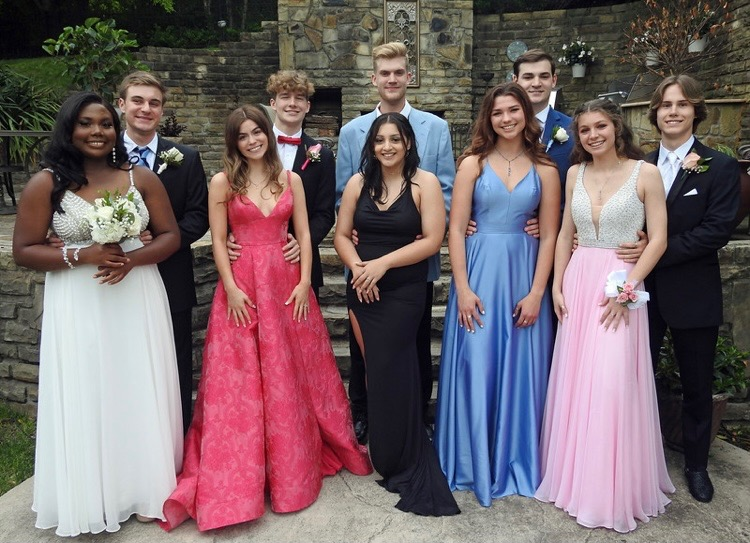A group of seniors taking pictures together at a house before leaving for dinner and the dance.