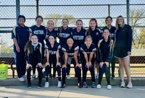 Middle School Softball team smiles for picture after winning the game.