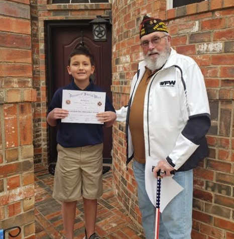 Sixth grader Jonathon Rincones-Peters receives his Patriot
